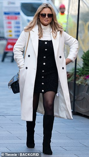 Seasonal style: Emily wore a white polo neck underneath a black dress with a cosy coat layered on top and her hair and make-up flawlessly coiffed