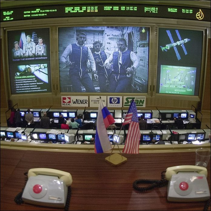 Shepherd, Gidzenko and Krikalevcan be seen on the screen on the ISS from this control centre picture showing the Russian and US flags in the foreground