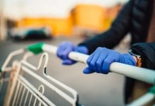 Close-up view of hands in rubber gloves pushing shopping carts.