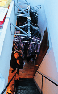 Nicole Chu, 20, hangs her wardrobe over her loft staircase. Her 200 square foot West Village micro-apartment requires her to walk through her makeshift closet in order to use the bathroom. (Henry Miller)