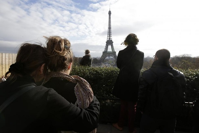 People observe a minute of silence at the Trocadero in front the Eiffel Tower to pay tribute to the victims of the series of deadly attacks on Friday in Paris, France, November 16, 2015. REUTERS/Philippe Wojazer