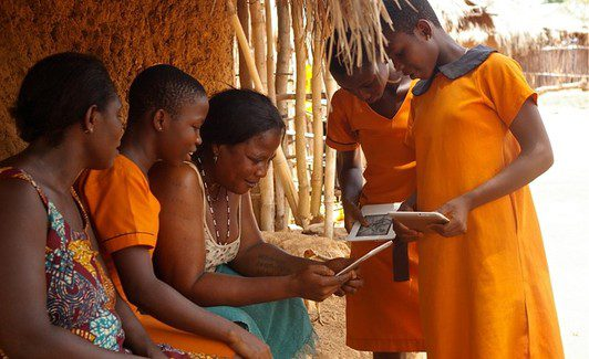 Worldreader.org Children in Ghana showing their e-readers to their parents. Most of the parents do not read, so Kindle capabilities like the built-in dictionary and text-to-speech help families.