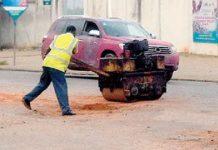 Men filling potholes just behind the scoreboard area of Baba Yara stadium on Friday morning