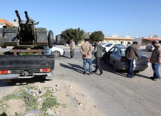 Libya Dawn fighters check passing cars near a local checkpoint in the al-Tusha area, west of al-Azizia, Libya, on April 3, 2015. Clashes continued in al-Azizia on Wednesday between pro-government forces and the Islamist armed coalition Libya Dawn. (Xinhua/Hamza Turkia)