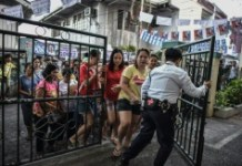 AFP / Mohd Rasfan A security guard opens the gates for voters to enter a polling station in Manila, on May 9, 2016