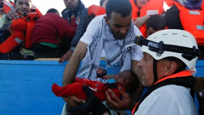 A migrant hands a baby from a wooden boat to a rescuer of the Malta-based NGO Migrant Offshore Aid Station (MOAS) during a rescue operation in the central Mediterranean