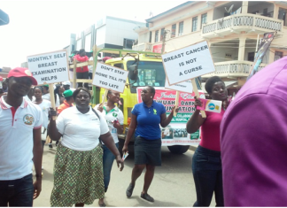 kdua004 Plaques bearing health works and breast cancer survivors in a float on the principal street of Koforidua