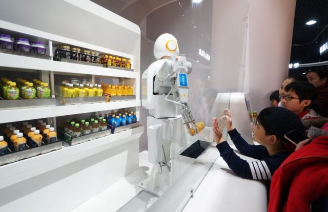 Pupils buy drinks from a robot salesman at a science and technology museum in North China's Tianjin on February 25. (Photo: CFP)