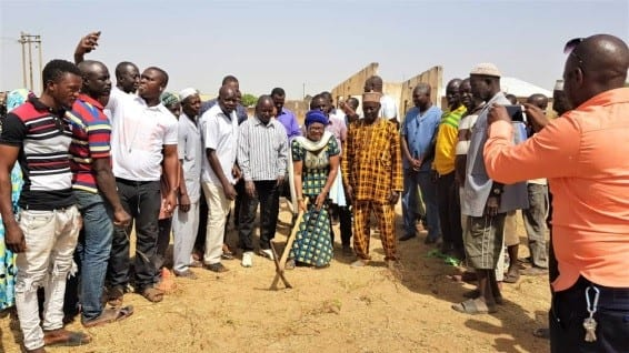 Bawku MCE Hajia Ninchemah middle holding the pick axe to cut the sod