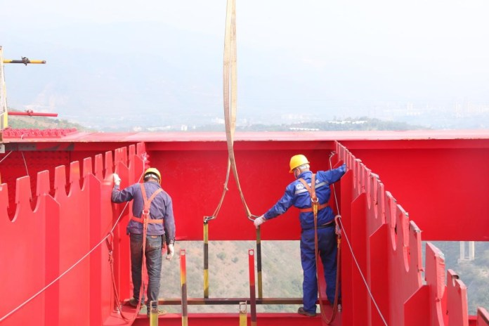 Construction workers help hoist a girder on the 230-meter-high Yuanjiang Railway Bridge along the Yuxi-Mohan section of China-Laos Railway. Photo by Ye Chuanzeng, Li Hong, People's Daily