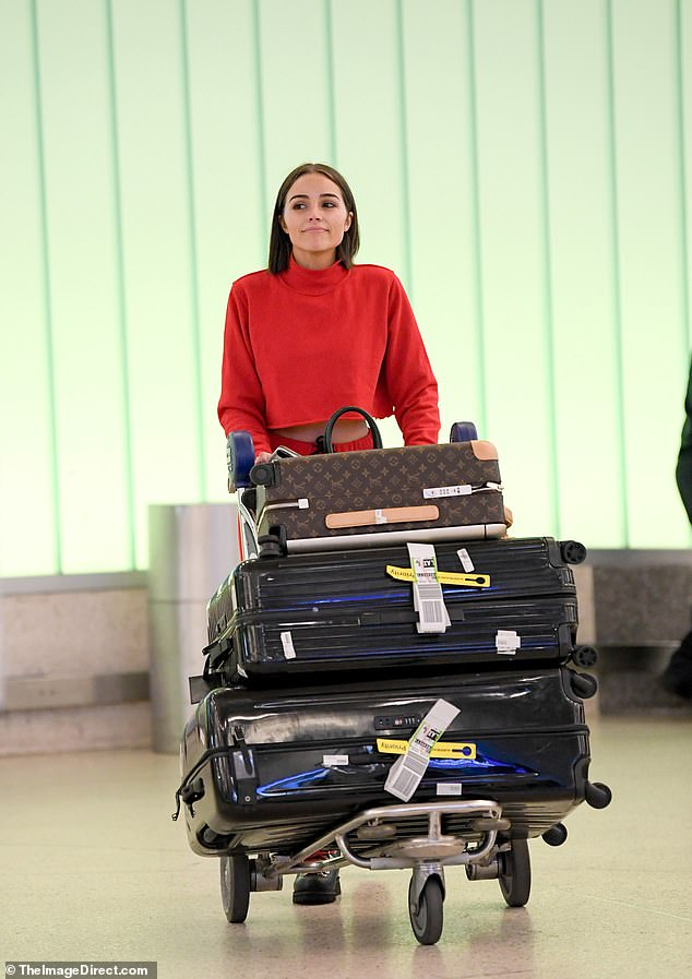 Packed: The 26-year-old former beauty queen paraded her svelte physique through the terminal wearing a bright red sweater and matching pants before wheeling away multiple cases of luggage