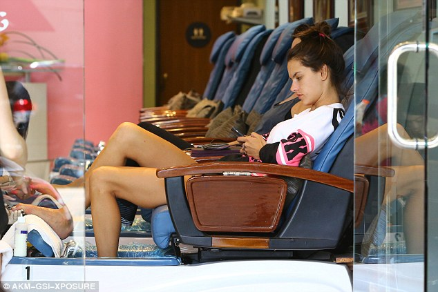 Time out: The supermodel checked her phone for messages during the pampering treatment