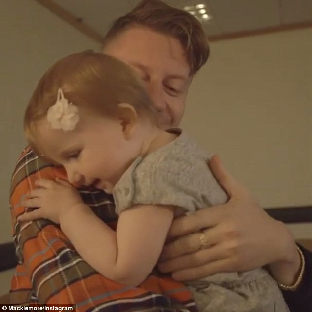 Proud dad: The tiny tot crawls toward them, with her papa eventually scooping her up off the ground. 'Yes, you did it!' he exclaims three times, hugging her in a sweet embrace