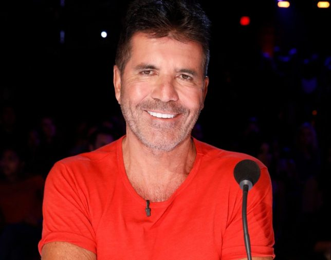 Simon Cowell smiles for the camera in a red top