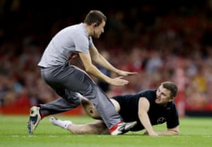 A pitch invader is tackled by a security staff member.