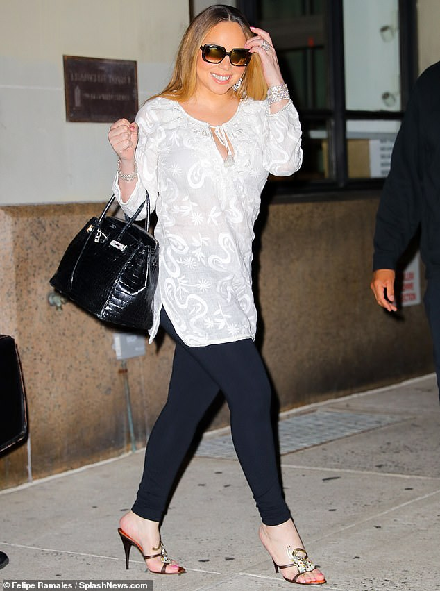 Always glam:Mariah looked slender in her chic outfit. He had on a long white top that tied in the front with a keyhole