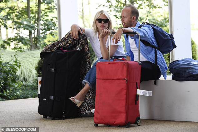 Catch ups: She chatted to her publicist Max Dundas as they sat with their luggage