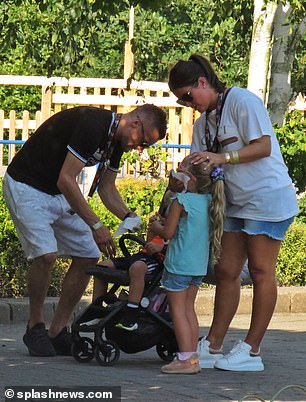 Clean up operation: Doting parents Rebekah and Jamie were seen wiping their children with wet wipes after the little ones no doubt indulged in some tasty snacks