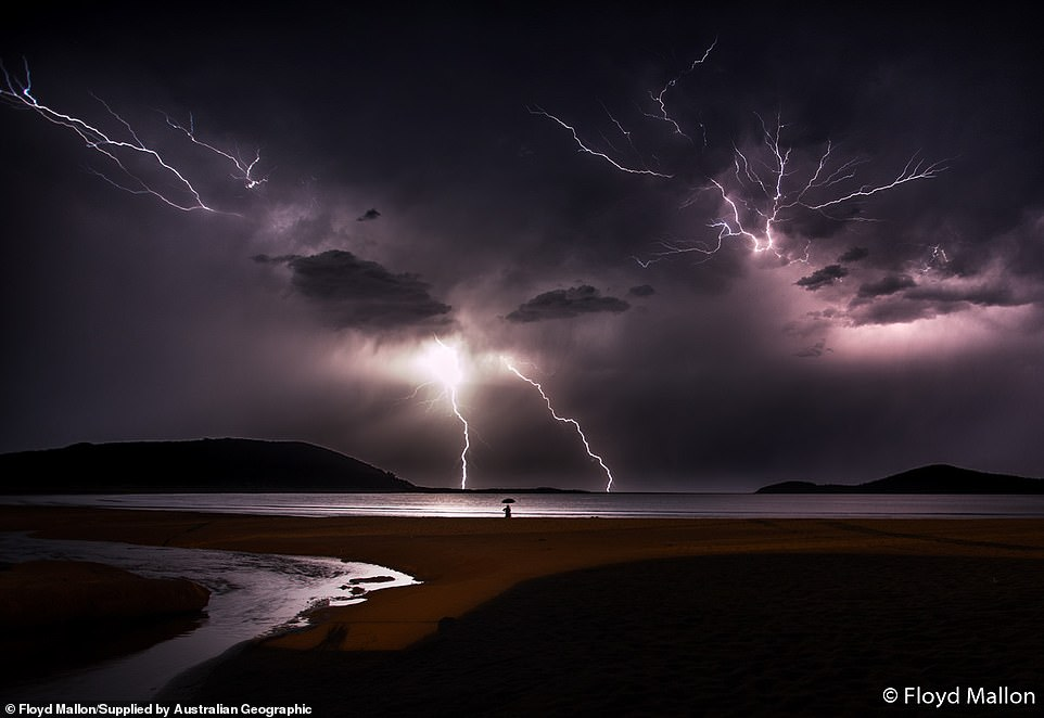 Floyd Mallon, 17, from New South Wales, witnessed this incredible weather atFingal Bay. 'For the composition, I decided to focus on a man standing at the edge of the water with an umbrella to add a sense of scale to the image,' he said.