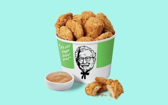 Bucket of KFC's plant-based 'chicken' nuggets on a turquoise background with a dip in front