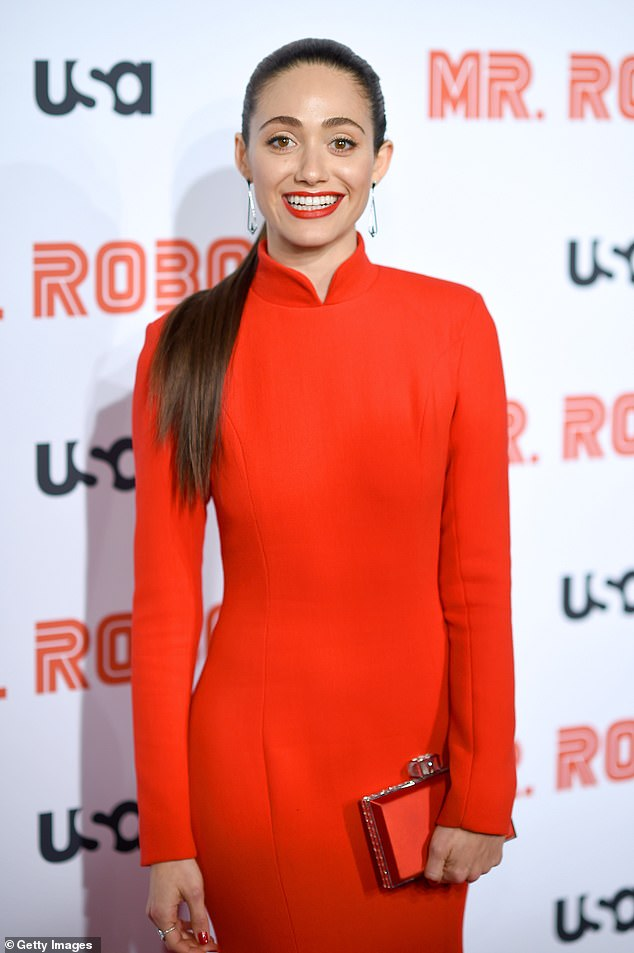 Monochrome: She matched the long sleeve and high-neck attire with a red and gold clutch and red lipstick