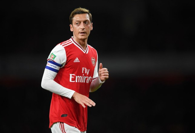 Mesut Ozil jogs as he plays for Arsenal