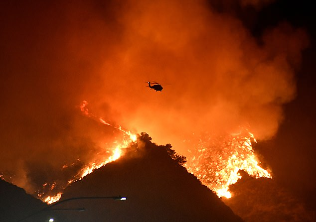 DailyMail.com spoke to two climate activists who explained the devastating health effects of breathing in wildfire smoke, including tiny particles that increase the risk of heart disease, asthma and cancer. Pictured: A firefighting helicopter flies over the Getty Fire as it burns in the hills of West Los Angeles, California on Monday