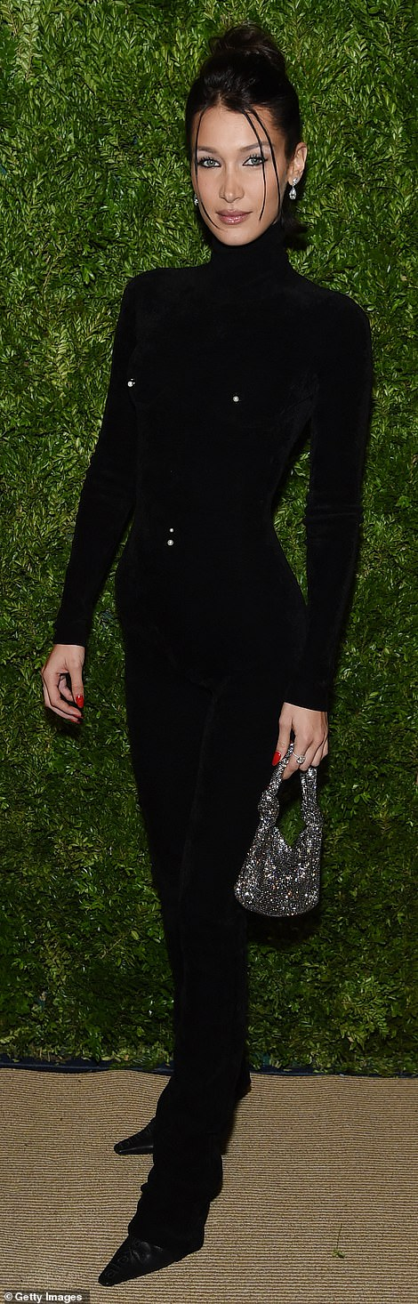 Bizarre look: Her younger sister Bella Hadid, 23, looked like a queen of the night in a black suit with intriguing fake piercings