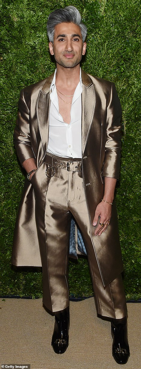 Shining:Queer Eye star Tan France looked stylish in a silky brown suit with a long evening coat and a partially unbuttoned white shirt