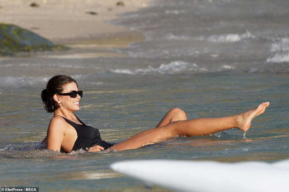 Impeccable: Georgia's classic black swimsuit put emphasis on her impossibly toned legs.