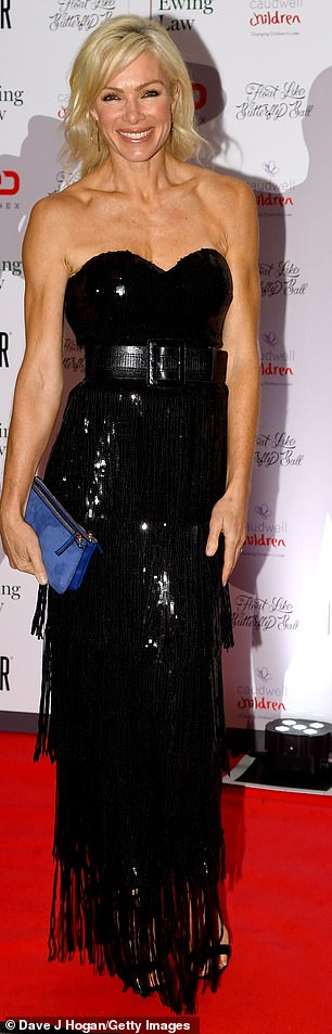 Glamorous: The beauty looked sensational in the belted number, while she paired with a blue suede clutch bag