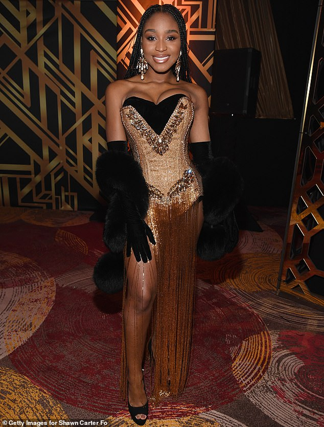 Swank: Normani cut a showstopping figure in a black and gold gown that featured opera gloves, a fur wrap and a layer of flapper-esque fringe