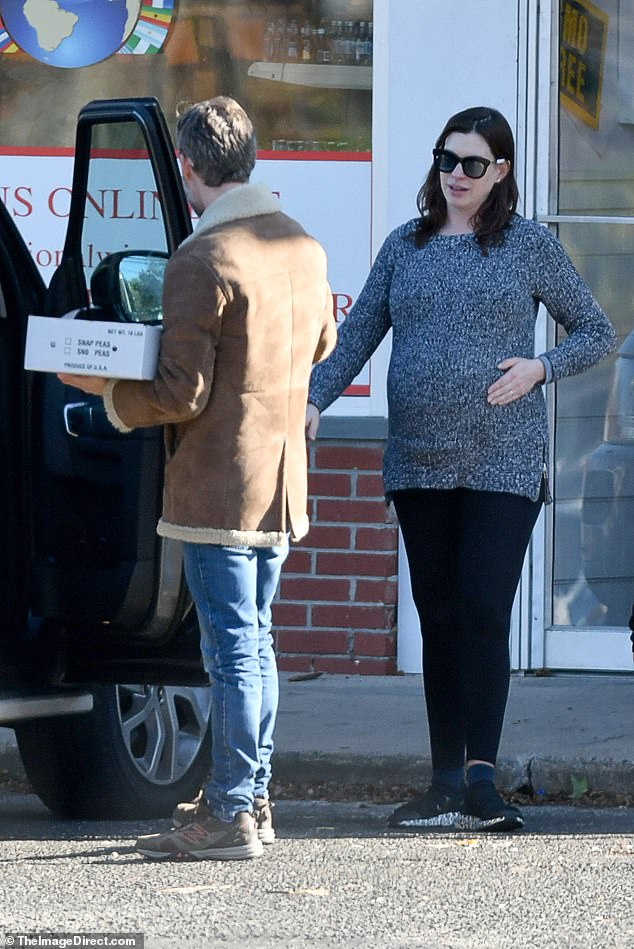 Baby on board! Anne Hathaway was positively beaming as she stepped out to run errands with her husband Adam Shulman in Connecticut on Monday morning