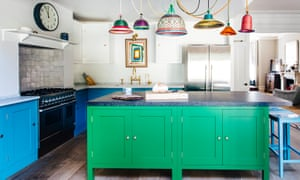 Bright green and bright blue kitchen cabinets with multicoloured hanging lights