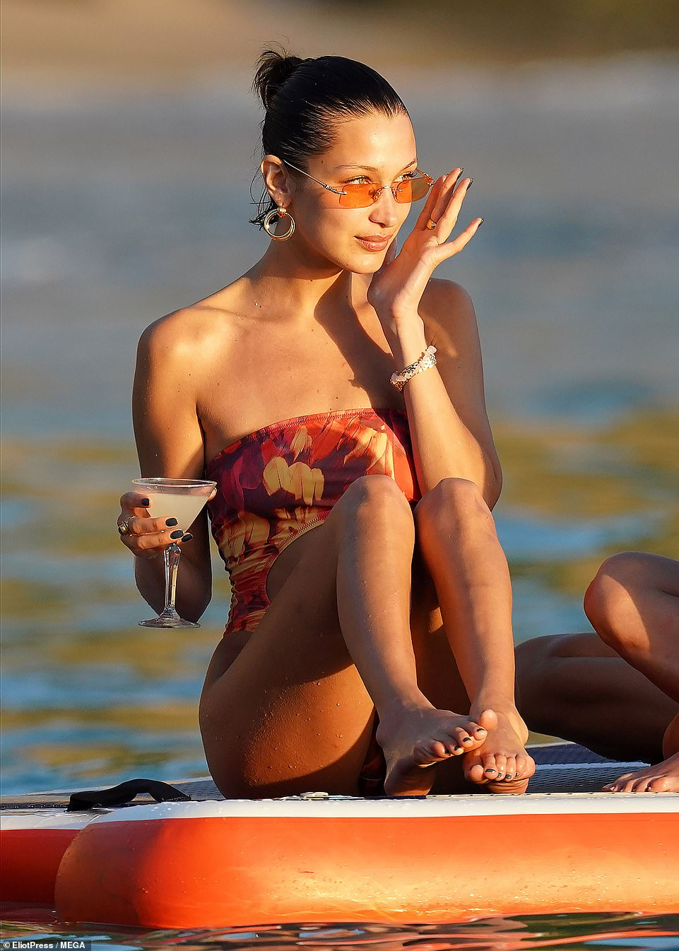 Sitting pretty:The supermodel, 23, accessorized with rectangular sunglasses featuring an orange tint as well as some hoop earrings