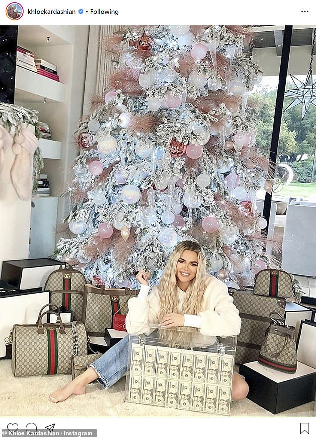 An ad: On Monday Khloe shared this post. She was in front of her pink and white tree. The caption said, 'Who wants $30,000 USD CASH + ALL the luxury bags pictured here with me?!! Just in time for the Holidays! #ad'