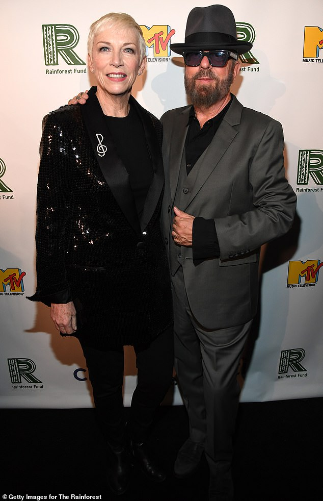 Reunited: Annie Lennox donned a black sequined blazer with a diamond treble clef broach, as Dave Stewart sported a grey three-piece suit with a black shirt and fedora