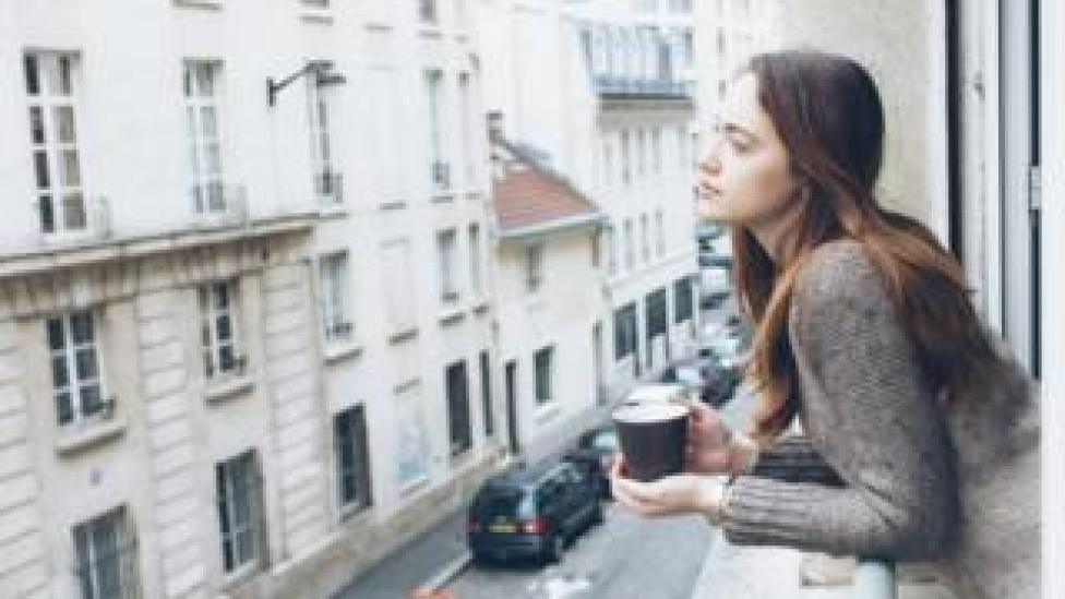 Young woman drinking coffee in a French flat