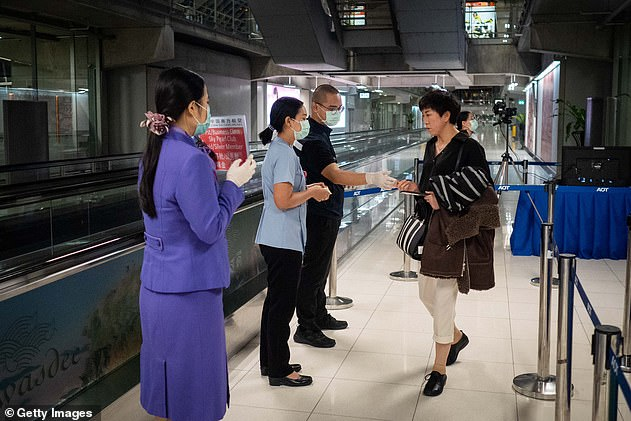 The second case in Thailand was reported on January 17. A 74-year-old tourist was intercepted at Thailand's biggest airport Suvarnabhumi. Pictured, Bangkok airport staff performing thermal scans on a traveller