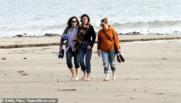 Wow factor: The group looked happy as they enjoyed a casual walk on the beach stateside