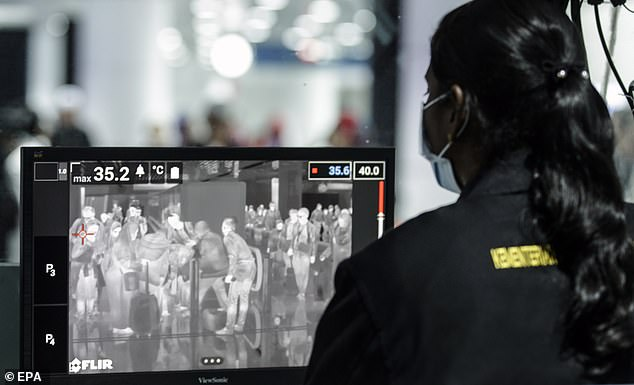 A Malaysia Health official checks passengers going through a thermal scanner upon their arrival at the Kuala Lumpur International Airport