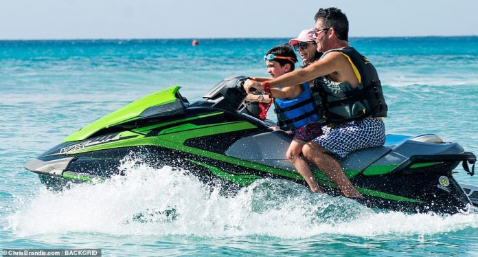 The best time: The trio were the image of the perfect family as they zipped about on the water together