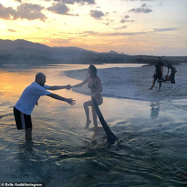 Scantily clad:In one shot, Hadid received a helping hand out of the shallow water while showcasing her slim 5ft9in figure in nothing more than a ruffled bikini