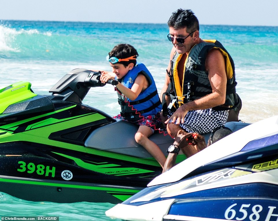 Giggles: Simon's lookalike boy giggles with glee as he sat on board the jet ski