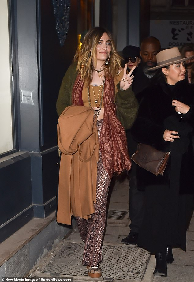 Peace out: The Chanel spokesperson flashed a peace sign as she was followed out by security