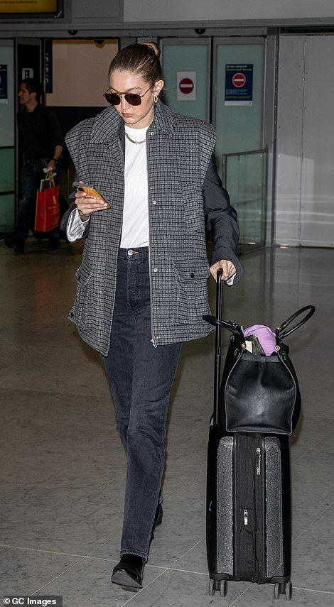 Simple: She donned a casual ensemble of a grey gilet and jeans with her blonde hair pulled back into a sleek bun.