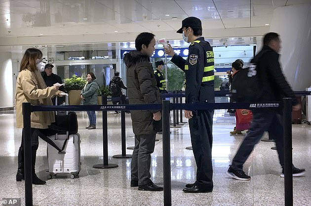 An official uses an infrared thermometer on a traveler at a health screening checkpoint at Wuhan Tianhe International Airport. Wuhan is at the center of the outbreak