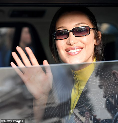 Cheerful: The star was in high spirits as she waved to the fans from the window of her car