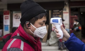 A community worker checks the temperature of courier in an Express station on 29 January in Hubei province.