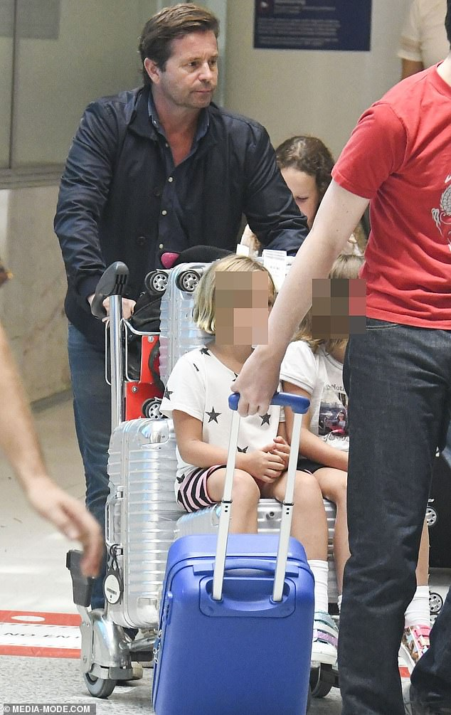 Back to reality: Steve appeared downcast as he pushed along a baggage trolley, on which his two daughters, Isabella, eight, and Francesca, six, were sitting